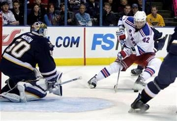 New York Rangers' Artem Anisimov, right, of Russia, tries to control a puck as St. Louis Blues goalie Chris Mason, left, defends during the first period of an NHL hockey game Saturday, Jan. 16, 2010, in St. Louis. (AP Photo/Jeff Roberson) By Jeff Roberson