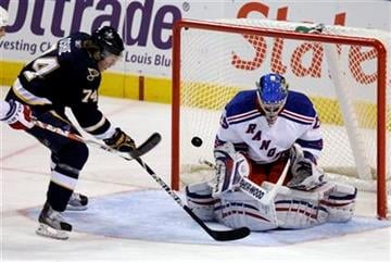 St. Louis Blues' T.J. Oshie, left, tries to get a shot off as New York Rangers goalie Chad Johnson defends during the third period of an NHL hockey game Saturday, Jan. 16, 2010, in St. Louis. The Blues won 4-1. (AP Photo/Jeff Roberson) By Jeff Roberson