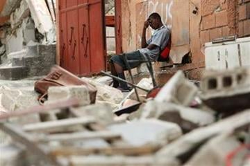 A man sits in front of an abandoned building in the aftermath of the earthquake in Port-au-Prince, Sunday, Jan. 17, 2010. (AP Photo/Gerald Herbert) By Gerald Herbert