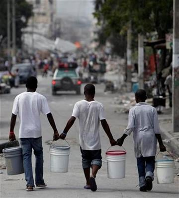 Men carry water in Port-au-Prince, Sunday, Jan. 17, 2010.  Relief groups and officials are focused on moving the aid flowing into Haiti to survivors of the powerful earthquake that hit the country on Tuesday. (AP Photo/Gregory Bull) By Gregory Bull