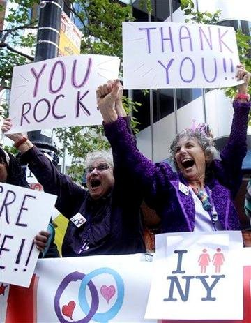 Shelly Bailes, left, and Ellen Pontac, who were married in 2008, hold up signs as marchers walk past in the 41st annual Gay Pride parade in San Francisco, Sunday, June 26, 2011. (AP Photo/Jeff Chiu) By Jeff Chiu