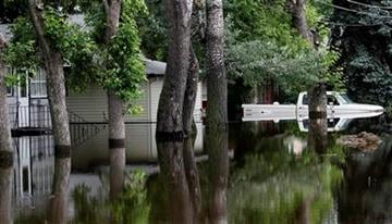 Flood waters from the Souris River surround a home and truck in the Oak Park neighborhood of Minot, N.D., Sunday, June 26, 2011. (AP Photo/Charles Rex Arbogast) By Charles Rex Arbogast