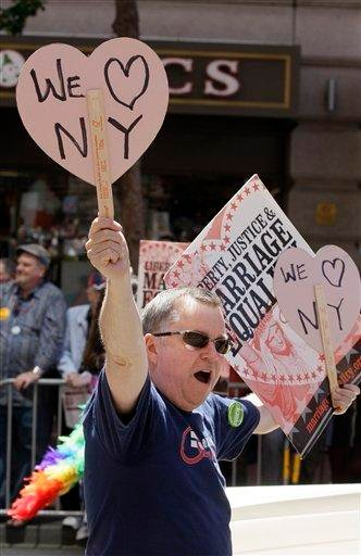 Lee Moulton holds up signs supporting New York while marching with Marriage Equality California during the 41st annual Gay Pride parade in San Francisco, Sunday, June 26, 2011. (AP Photo/Jeff Chiu) By Jeff Chiu