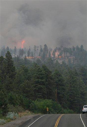 Flames are visible on a ridge facing Pajarito off of state road 501 during the second day of the Las Conchas Fire in  Los Alamos on Tuesday, June 28, 2011.  (AP Photo/Jane Phillips - The New Mexican) By Jane Phillips
