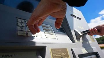 A woman uses a Wells Fargo walk-up Automated Teller Machine, or ATM. By Stephanie Baumer