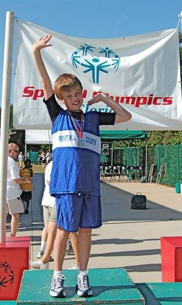 Inspiring an athlete -- Here, a 12-year-old John shows off his first-place medal for the 100 meters at the Special Olympics Summer State Games in 2008. By Courtesy Rachel Miller