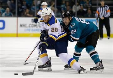 SAN JOSE, CA - JANUARY 03:  Ian Cole #28 of the St. Louis Blues and Barclay Goodrow #89 of the San Jose Sharks go for the puck at SAP Center on January 3, 2015 in San Jose, California.  (Photo by Ezra Shaw/Getty Images) By Ezra Shaw