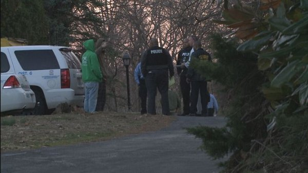 Authorities speak with people on the scene of an evening shooting on Tuesday.