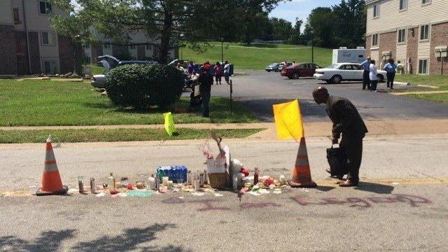 A man stops and bows his head in prayer at the scene of Michael Brown's death in Ferguson, Thursday, August 14, 2014.
