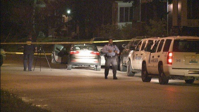 Police investigate a scene after a man was shot in both arms while sitting in a car.