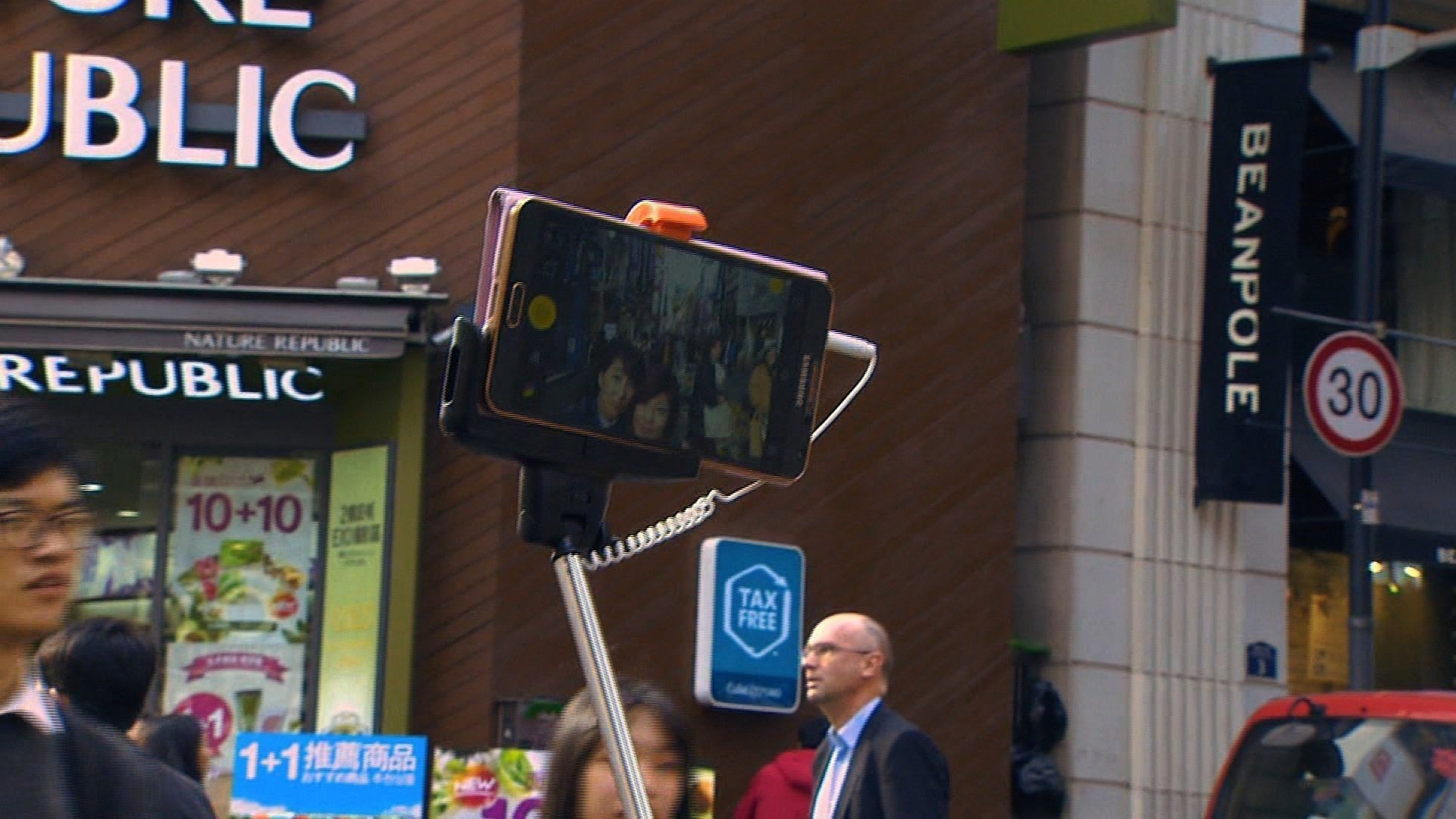 (Credit: CNN) A couple in Hong Kong uses a selfie stick, a long pole used to extend their camera phone more than three feet away allowing a wide frame for the photograph.