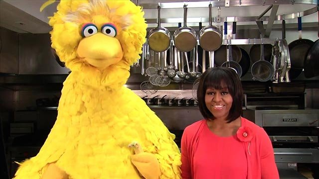 """(Credit: Lawrence Jackson/The White House) irst Lady Michelle Obama participates in a """"Let's Move!"""" and """"Sesame Street"""" public service announcement taping with Big Bird in the White House Kitchen, Feb. 13, 2013"""