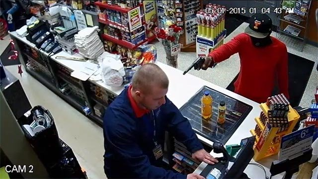 A suspect is seen on surveillance robbing a West Alton gas station Friday