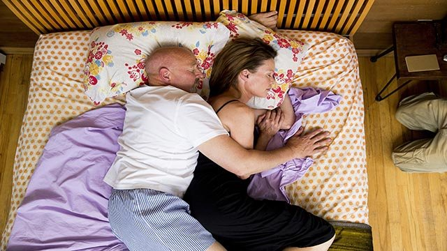 (Credit: George Lange/Turner Broadcasting) A stock photo showing a man and woman lying in bed, embracing.
