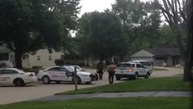 Police surround a Fenton home in a stand-off with a barricaded subject on Thursday.