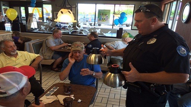 A Pacific cop serves coffee to residents at McDonald's.