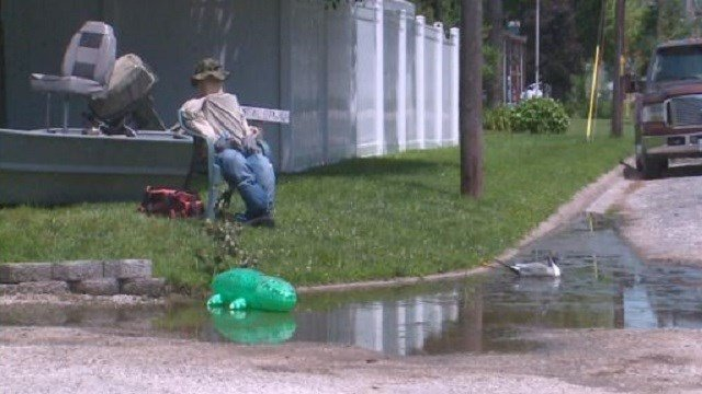 A Marissa man put a fishing boat and fisherman in his yard and false duck and alligator in the water to draw attention to the drainage issue.