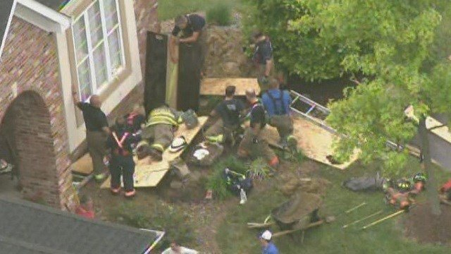 Emergency responders work to free a worker trapped in a trench collapse in Maryville.