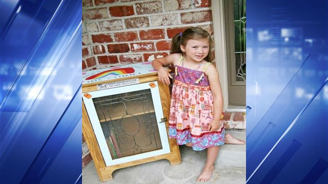 """Reese poses with her """"Little Free Library."""""""
