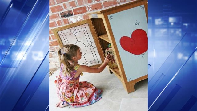 "Reese selects a book from her ""Little Free Library."""