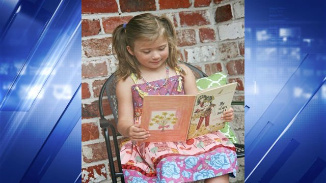 "Reese reads a book from her ""Little Free Library."""