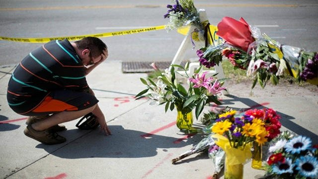 Noah Nicolaisen, of Charleston, S.C., kneels at a makeshift memorial, Thursday, June 18, 2015, down the street from where a man opened fire Wednesday night during a prayer meeting inside the Emanuel AME Church, killing several people.
