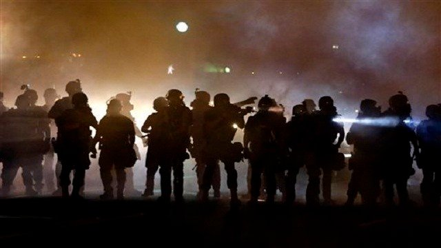 Police walk through a cloud of smoke as they clash with protesters in Ferguson, Mo. (AP Photo/Jeff Roberson, File)