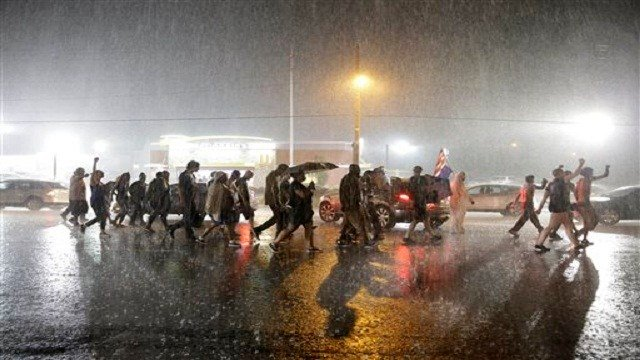 Protesters march in the rain, Sunday, Aug. 9, 2015, in Ferguson, Mo. Sunday marks one year since Michael Brown was shot and killed by Ferguson Police Officer Darren Wilson. (AP Photo/Jeff Roberson)