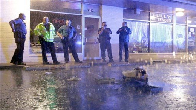 Police stand near a broken cash register in a parking lot after the front windows of a business were broken out along West Florissant Avenue. (AP Photo/Jeff Roberson)
