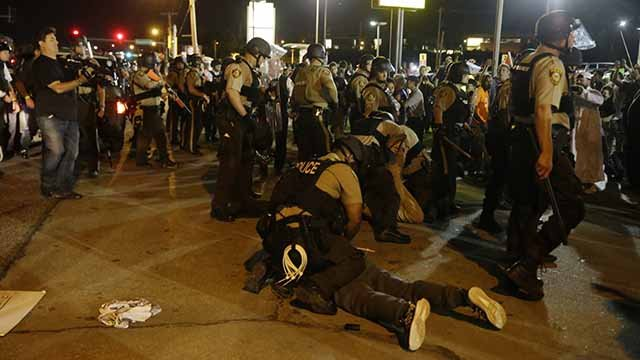 St. Louis County Police arrest people along West Florissant Avenue, Monday, Aug. 10, 2015, in Ferguson, Mo. Ferguson was a community on edge again Monday, a day after a protest marking the anniversary of Michael Brown's death was punctuated with gunshots.