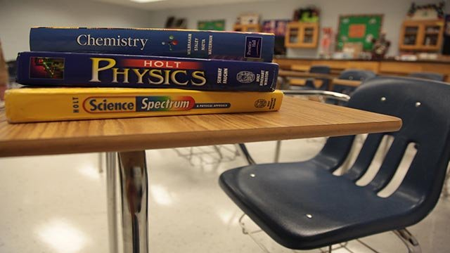 A file photograph showing chemistry, physics and science textbooks sitting on an empty student desk inside an Atlanta, Georgia school. (Credit: Ferre Dollar/CNN)