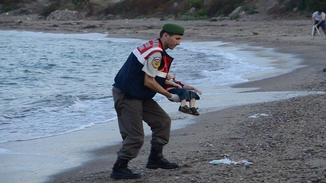 Authorities in Bodrum, Turkey, stand near the body of a child who washed ashore on Wednesday, September 2. The child was one of 12 refugees who drowned during a failed attempt to sail to the Greek island of Kos.