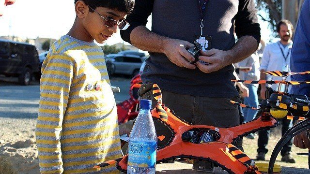 A young drone fan checks out the Game of Drones damage-resistant flying vehicle, which can withstand paintball hits, shotgun blasts and baseball bats.
