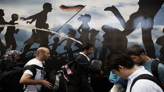 Immigrants walk by a train on which are visible people hugging and running on September 3, 2015.