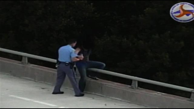 A North Carolina police officer on his way home from work extended a hand of compassion to a man hanging over a highway bridge Wednesday evening, September 9, 2015.  (Credit: North Carolina DOT)