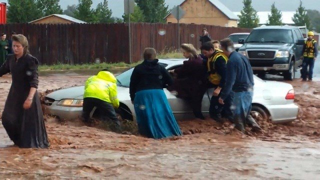 Fire and rescue workers pull a woman from a car in knee-deep flood water in the town of Hildale, Utah along the Arizona border on Monday, September 15, 2015.