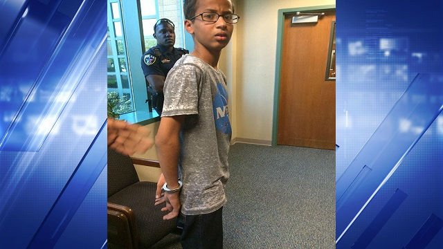 A photo shows Ahmed, wearing a NASA t-shirt, looking confused and upset as he's being led out of school in handcuffs.