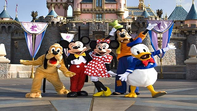 The classic Disney characters welcome visitors outside Sleeping Beauty Castle at Disneyland in Anaheim, Calif. (L-R) Pluto, Mickey Mouse, Minnie Mouse, Goofy and Donald Duck. (Credit: Scott Brinegar/Disneyland)