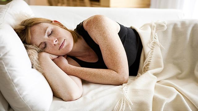 Stock image of a woman sleeping on the couch. (Credit: Amanda Greene/CNN)