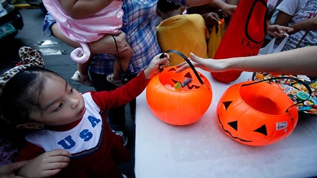 "Children queue up for candies and sweets in the annual ""Trick or Treat"" tradition on Halloween Monday, Oct. 31, 2011 at a subdivision at the financial district of Makati city east of Manila, Philippines. (AP Photo/Bullit Marquez)"