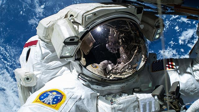 """NASA astronaut Barry """"Butch"""" Wilmore, Commander of Expedition 42 on Feb, 21, 2015 is caught by the camera as the Earth's surface passes by in the background. (Credit: NASA)"""