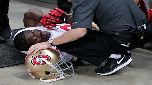 San Francisco 49ers running back Reggie Bush is attended to by a trainer after he slipped out of bounds after running the ball during the first quarter of an NFL football game against the St. Louis Rams, Sunday, Nov. 1, 2015, in St. Louis. (AP Photo/Tom G