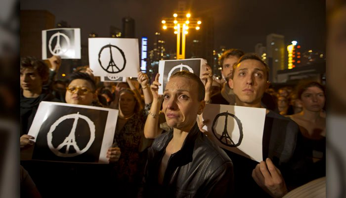 People gather in Hong Kong, Saturday, Nov. 14, 2015, to mourn for the victims killed in Friday's attacks in Paris. French President Francois Hollande said more than 120 people died Friday night in shootings at Paris cafes.