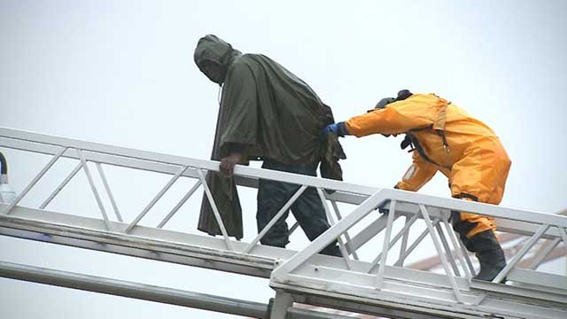 A firefighter helps one of the homeless men down the ladder.