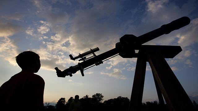 Matthew Hubbard, 10, from Grand Blanc, Mich., looks at Jim Podpolucha's 6 foot, f/15 homemade achromatic refractor telescope as the sun sets June 24, 2006 (Credit: AP Photo/Carolyn Kaster)
