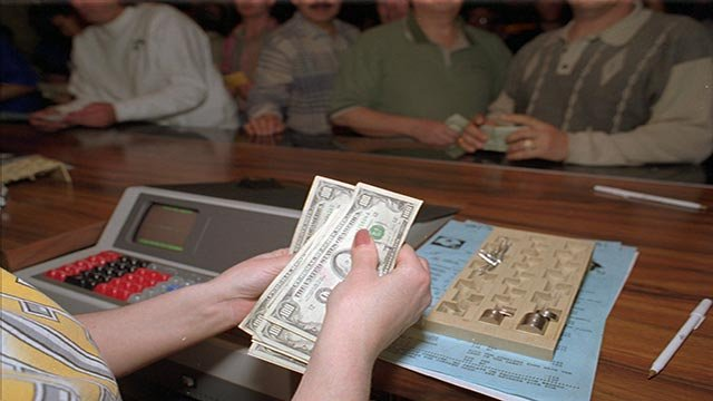 As people line up to place ther bets, a cashier counts out a number of $100 bills just wagered on the Super Bowl at the Mirage hotel and casino's sports book in Las Vegas, Sunday, Jan. 28, 1996. (Credit: AP Photo / Lennox McLendon)