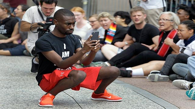 In an Aug. 10, 2015 file photo, protester and social media activist DeRay McKesson records outside the Thomas F. Eagleton Federal Courthouse Monday, in St. Louis. (Credit: Ap Photo / Jeff Roberson, File)