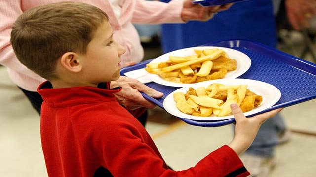 A young parishioner carries plates filled with fried fish and potatoes to a table during the Lenten Friday fish fry at St. Frances Cabrini Catholic Church in Littleton, Colo., on Friday, March 13, 2009. (AP Photo/David Zalubowski)