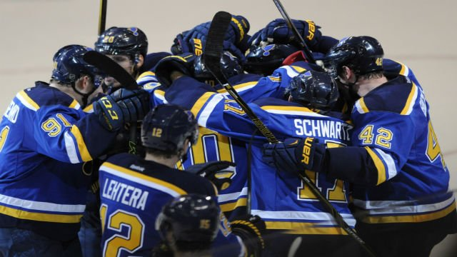 St. Louis Blues surround teammate Kevin Shattenkirk after his game winnning goal in overtime against the Dallas Stars during in an NHL hockey game, Tuesday, Feb. 16, 2016, in St. Louis. The Blues won 2-1. (AP Photo/Bill Boyce)