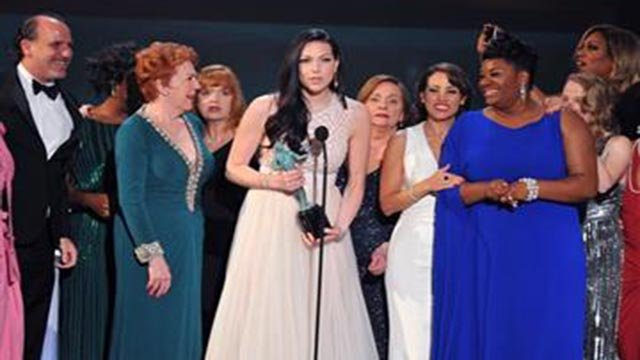 "(Photo by Vince Bucci/Invision/AP, File). FILE - In this Jan. 30, 2016 file photo, Laura Prepon, center, and the cast and crew of ""Orange is the New Black"" accept the award for outstanding ensemble in a comedy series at the 22nd annual Screen Actors Guild"
